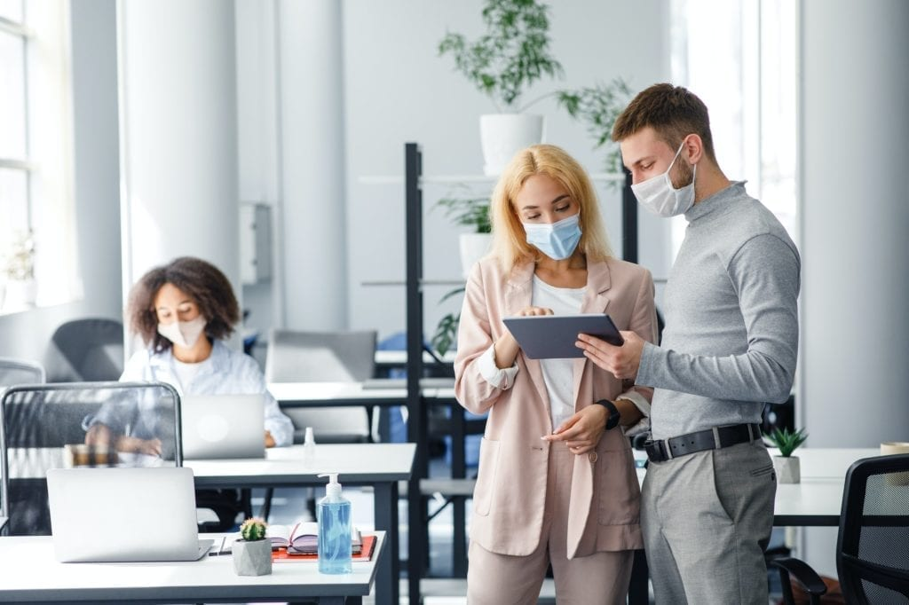 Colleagues in protective masks discuss project and look at tablet in coworking office